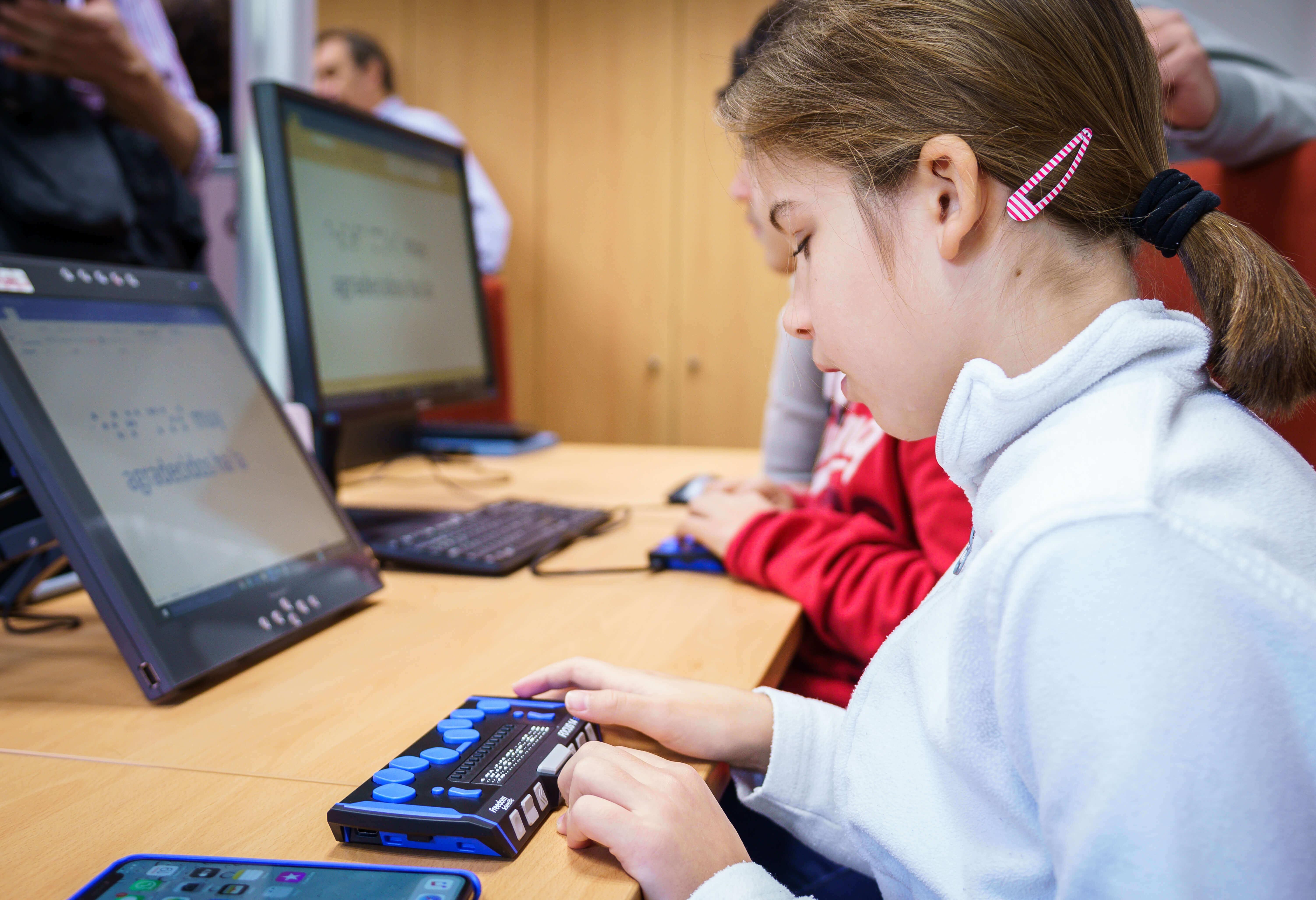 Menores usando la línea Braille