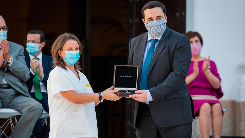 El coordinador de RedCor, David González, recibe la Medalla de manos de la limpiadora de OHL Servicios Integrales Ángela Aguilar. Foto: Junta de Extremadura