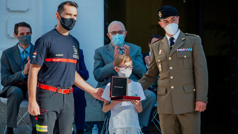 Jorge Díaz, de 12 años, recoge la Medalla de Extremadura de manos del bombero del Parque Comarcal de Mérida Martín Serván, y el Cabo Primero de la Brigada de Infantería Mecanizada 'Extremadura XI' Juan Pedro Tejada. Foto: Junta de Extremadura