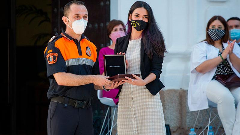 El voluntario de Protección Civil Miguel Ángel Polo entrega la Medalla a la voluntaria del Operativo Alpha María José Gómez. Foto: Junta de Extremadura
