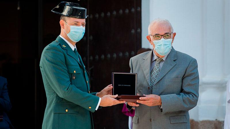 El presidente de la Cooperativa Servimayor, Martín González, recibe la Medalla de manos del agente de la Guardia Civil José Luis López. Foto: Junta de Extremadura