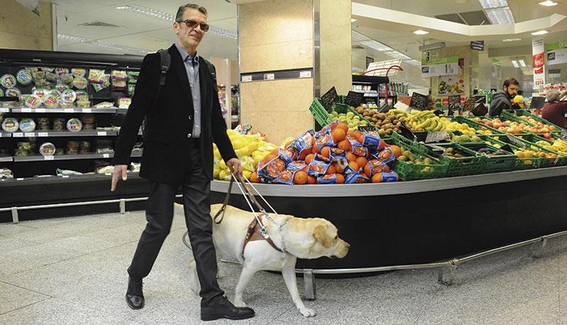 Una persona ciega con su perro en el supermercado. Foto: Fundación ONCE del perro guía